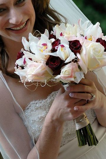 Fresh hand tied bouquet of roses and orchids with a wire collar.