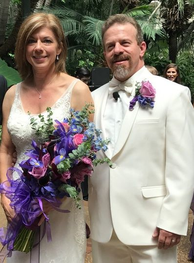 Newlyweds with pink and violet flowers