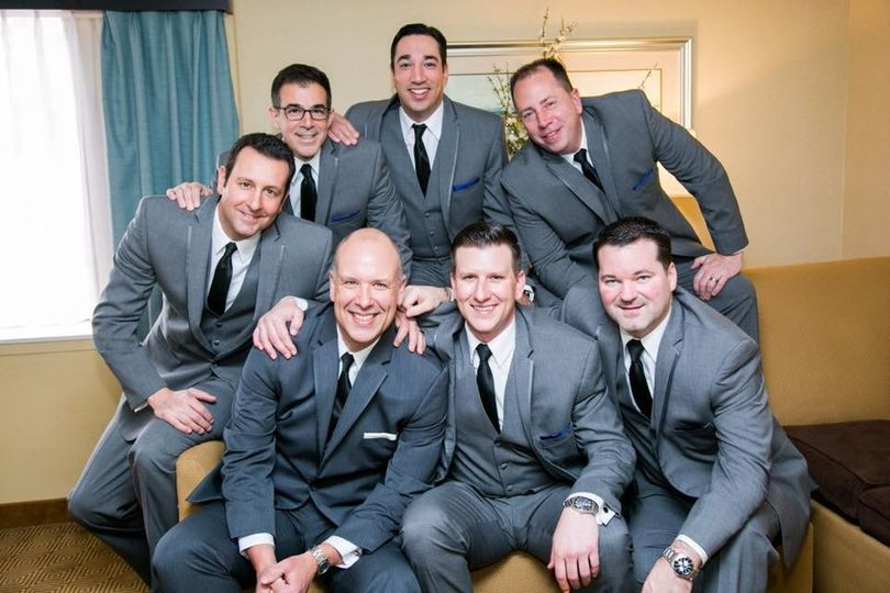Groom and groomsmen with matching three-piece suits