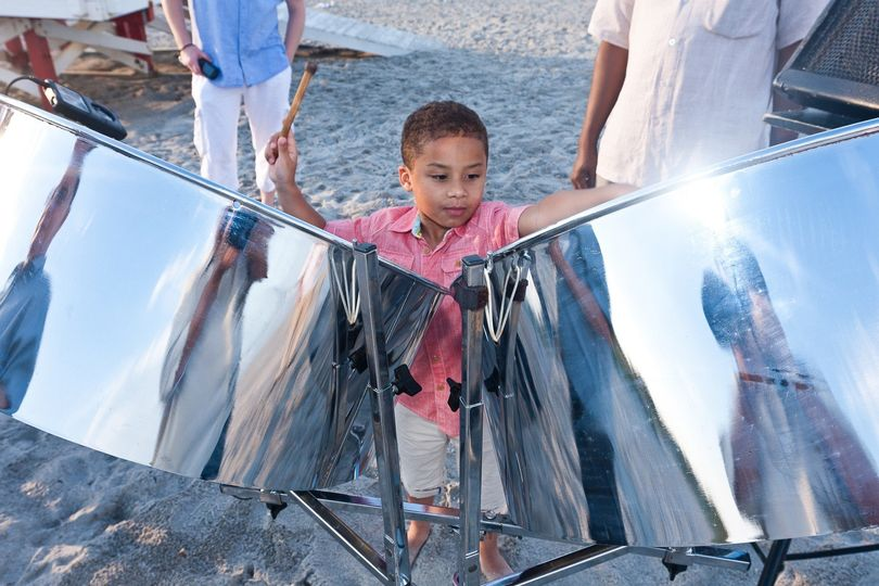 Kid having fun on the steel drums at a beach wedding ceremony in Cocoa Beach FL.