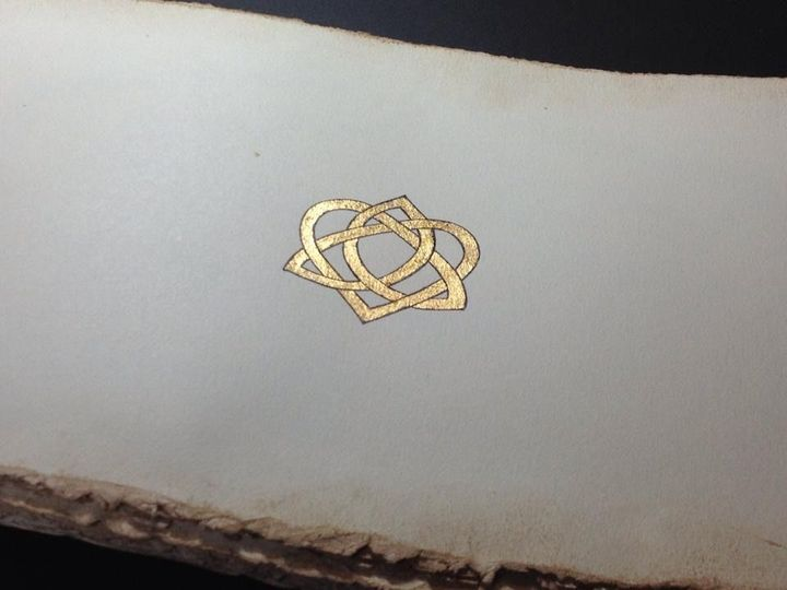 Gold leaf and a bit of Celtic knotwork adorn an opening page in a fairytale style hand-bound wedding...