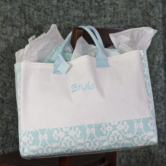 "The only bag the bride will need!  A generous, canvas tote with the word ""bride"" embroidered on the..."