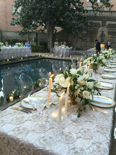 Wedding reception tables featuring white flowers and greenery in antique compotes for a classic...