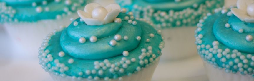 Turquoise cupcakes with gum paste flowers and pearls.