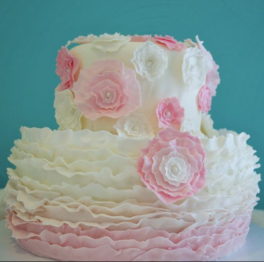 Pink and white ruffle ombre cake with pretty flowers.