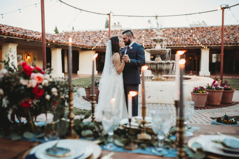 Newlyweds dance by candle lit table