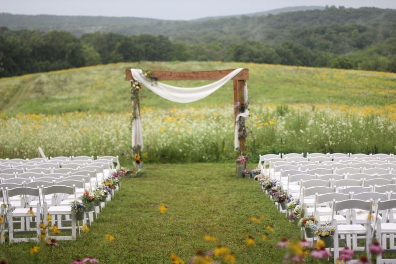 View of floral designs for arbor and aisle bouquets for a mid-summer outdoor wedding.