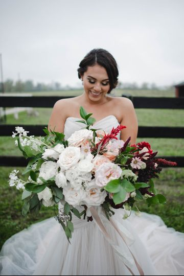 800x800 1511989258953 bride smiling and admiring her bouquet