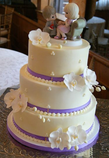"Buttercream wedding cake with gum paste orchids, violet ribbon, and Precious Moments ""Will You Share..."
