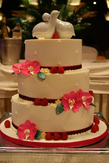 Lemon cake with raspberry filling and almond buttercream, adorned with fresh raspberries & sculpted...
