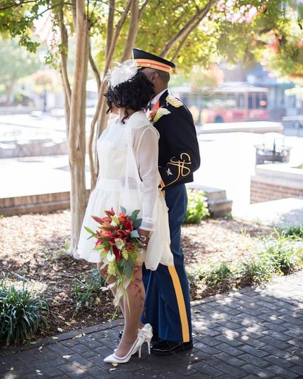 Newlyweds kissing by the tree
