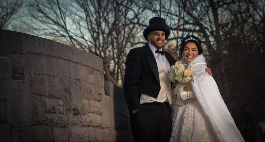 Newlyweds beside a stone wall