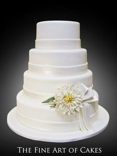 An elegant all white tiered cake featuring a large, detailed sugar delilah flower and ribbon....