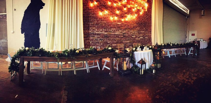 The couple with the bridesmaids and groomsmen table setup