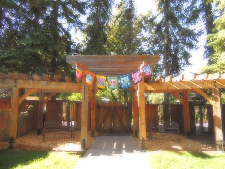 Backyard pergola with rainbow flags at UCC of Missoula, Missoula MT