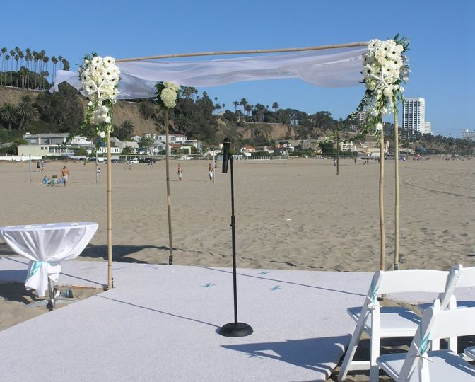 A full view of the simple but elegant beach canopy.  Adorned with hydrangeas, roses, white gerbers...