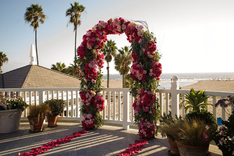 A view of the Santa Monica Beach in the background of the wedding ceremony arch.  This arch is full...