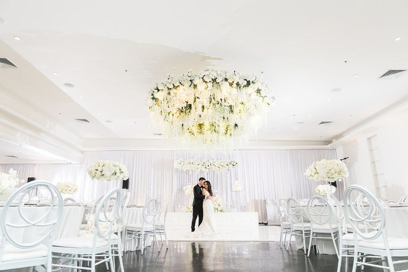 Newlyweds under the floral chandelier