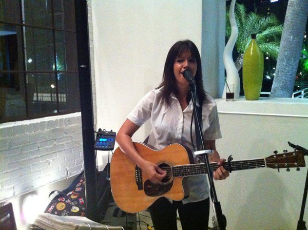 A woman playing a guitar and singing