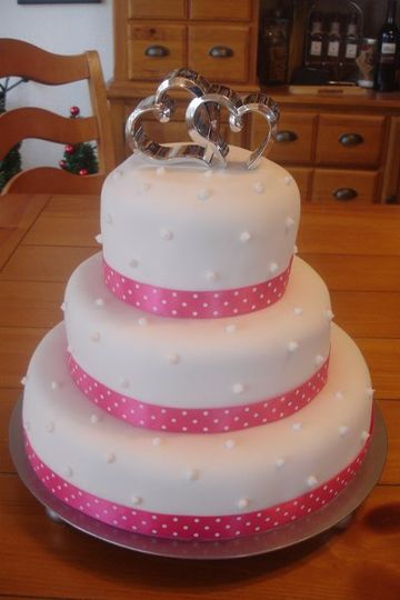 A pretty fondant cake with a metal keepsake topper, wrapped in satin ribbon