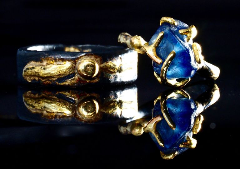 natural blue sapphire mounted in 18k gold and oxidized silver band accompanied by man's wedding band...