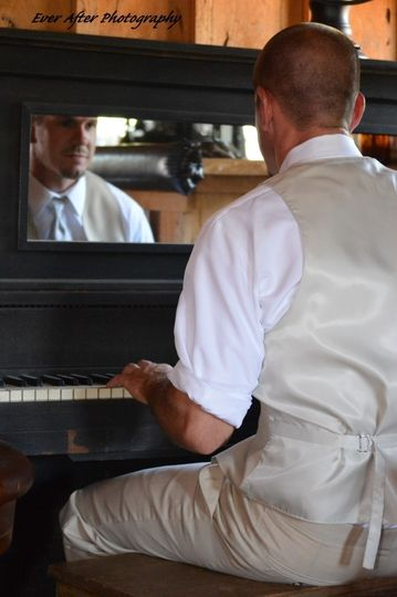 groom sitting at piano in saloon before wedding
