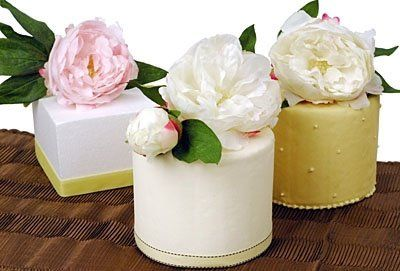 Three centerpiece cakes with hand crafted peonies atop fondant covered cakes of strawberry cream,...