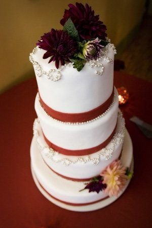 Pumpkin cake with tangy cream cheese frosting enrobed in burgandy wine colored fondant and graced...