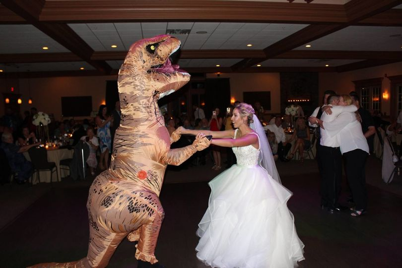 Bride dance with the dinosaur mascot