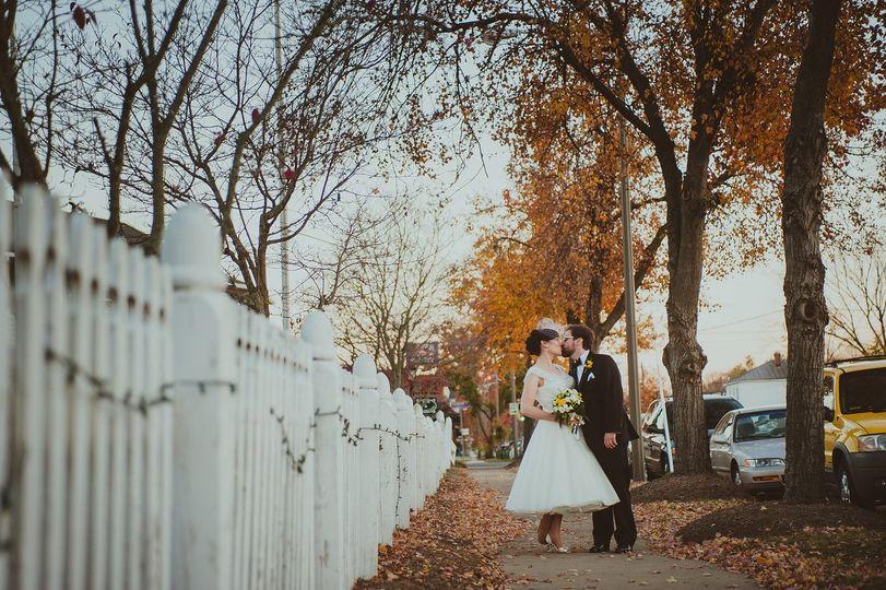 Newlyweds kissing on the sidewalk