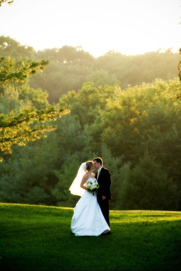 Bride and groom kissing on the field