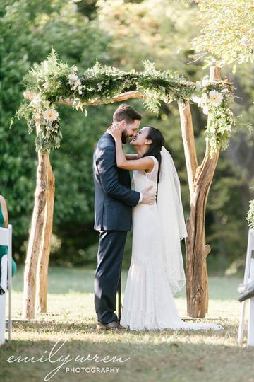 Couple kiss under wedding arch