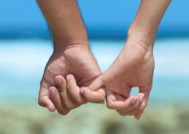 couples holding hands at beach