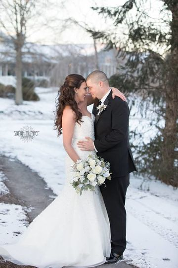 Newlyweds kiss in the snow | Gown: Alfred Angelo