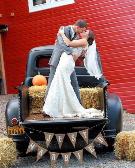 Wedding kiss on top of truck | Gown: Rebecca Ingram