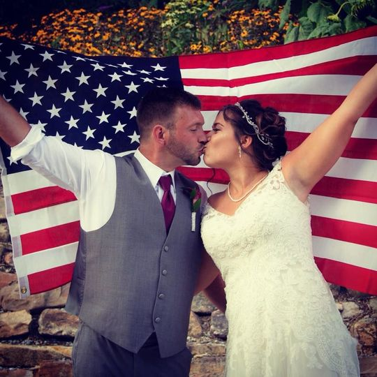 Newlyweds and the American flag | Gown: Casablanca