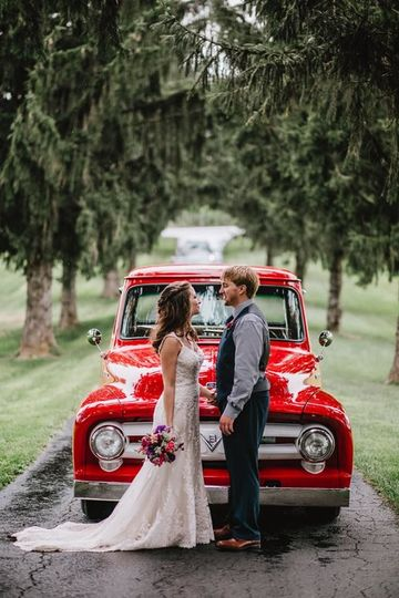 Newlyweds in front of red wedding car