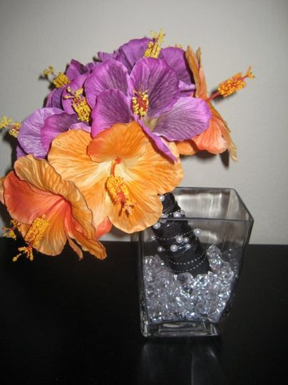 This centerpiece consists of a retangular vase which is about 6 inches high. It is filled with...