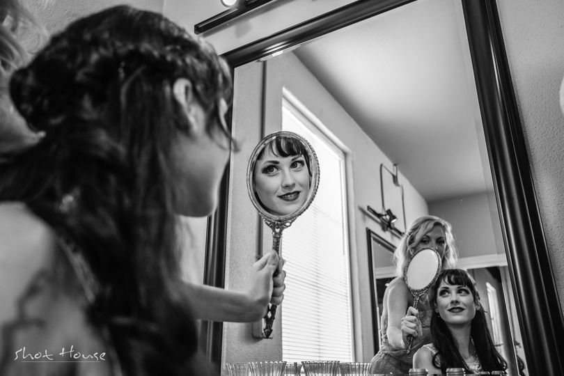 The maid of honor helps the bride prepare for her ceremony by showing her the beautiful makeup and...
