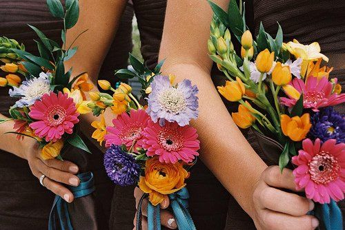 To complement the bride's bouquet, the attendants carried similar, more colorful bouquets also in a...