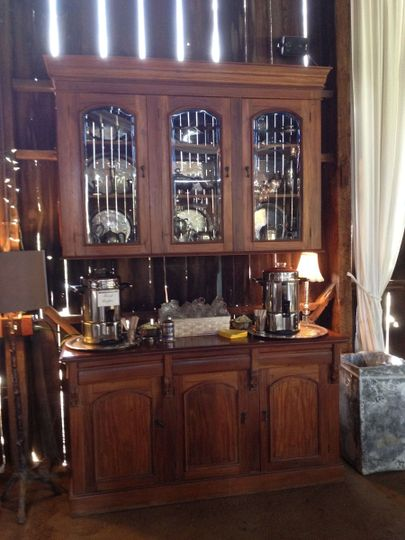 A coffee bar set up on an elegant cupboard which is a permanent antique piece in our barn