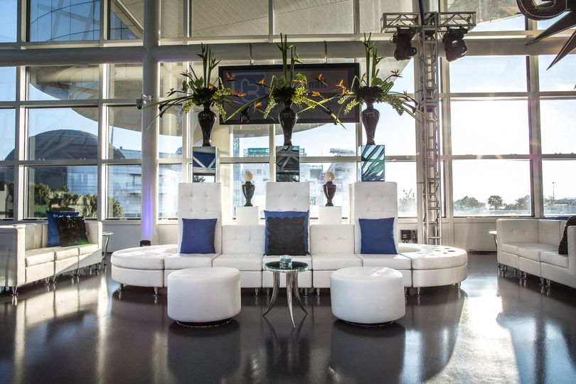 """Our large """"Racetrack"""" lounge design with low back sofas, ottomans, end tables, and pillows."""