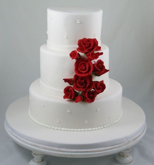 All white wedding cake with red roses