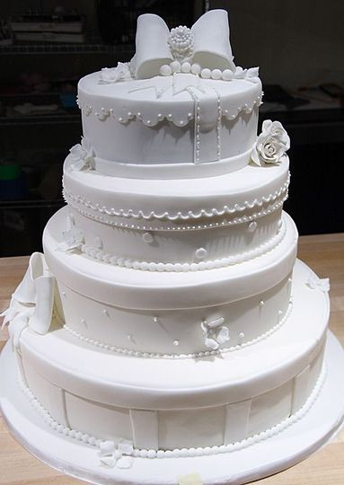 All white wedding cake with bow on top