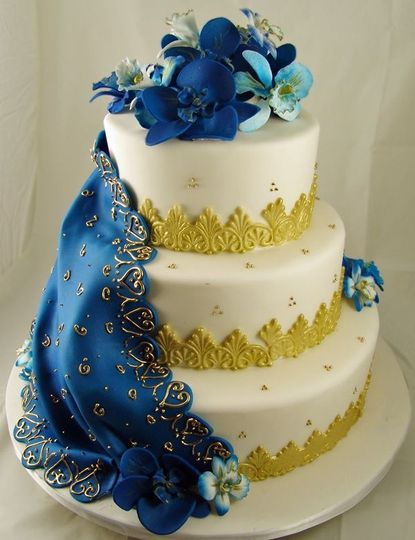 Wedding cake with blue flowers on top