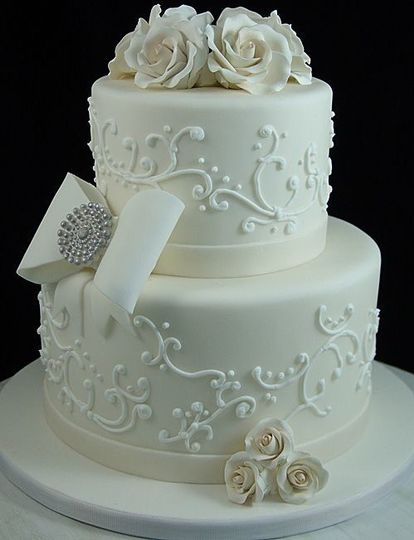 All white wedding cake with white roses on top