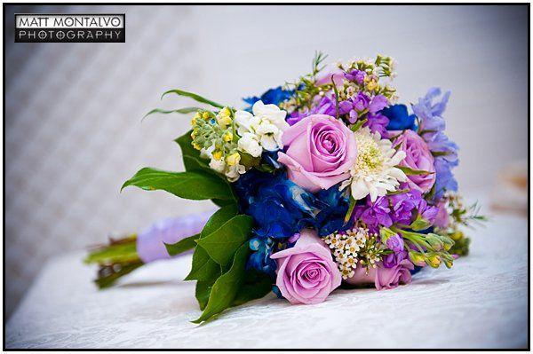 Bridesmaid bouquet with roses, scabiosa, delphinium, stock, and bright blue hydrangea.