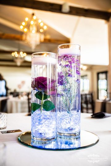 "The ""Bethann""Glass vases filled with water, silk purple flowers, floating candles and clear stones..."