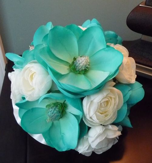 Hand Painted Magnolias dominate this soft Bridal Bouquet interspersed with Creamy Ranunculus.  The...