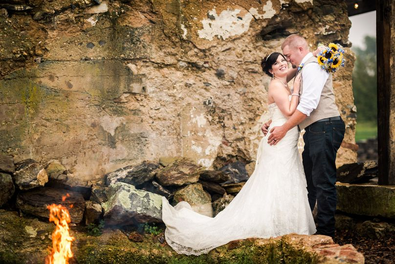 Crissy & Pat steal a moment beside the barn ruin and fire pit.
